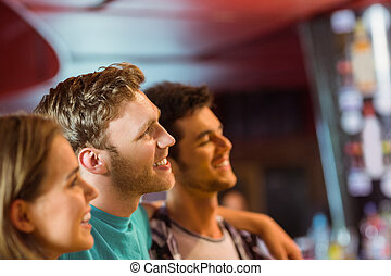 Smiling brown hair standing with arm around his friends in a...