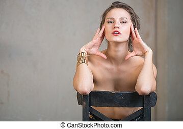 Sexy beautiful young woman sitting on a chair