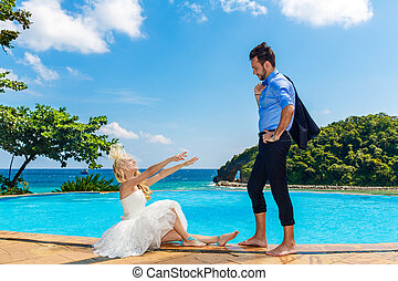 happy bride and groom poolside infinity Tropical sea in the...
