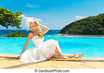 Beautiful young bride in a wedding dress sitting on the edge of