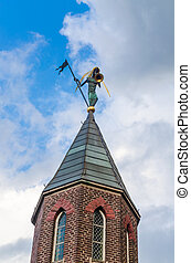 Church spire with trombonist before blue sky
