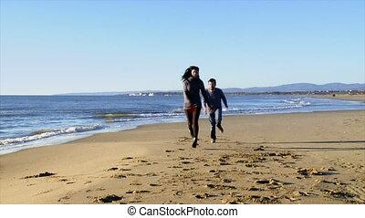 Happy couple on beach in winter run