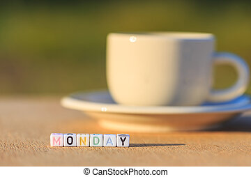 Monday written in letter beads and a coffee cup on table