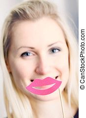 smiling woman with big paper lips in front of her mouth