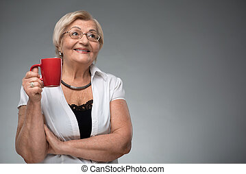 Elderly woman with cup of coffee - Retired and relaxed Happy...