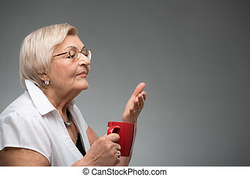 Elderly woman with cup of coffee - Enjoying the cup of...