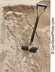 a construction shovel on sand
