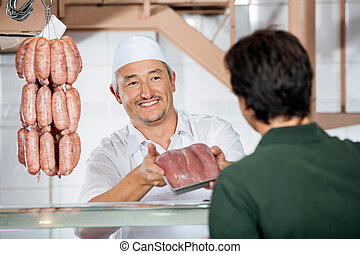 Butcher Showing Packed Sausages To Customer - Happy mature...