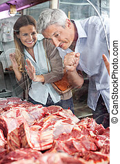 Couple Looking At Meat Through Cabinet In Butchery