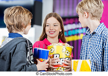 Siblings Conversing While Holding Snacks At Cinema - Cute...