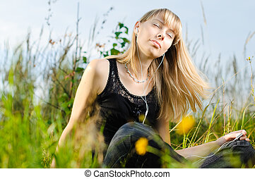 young girl - beautiful young girl sitting in the grass and...