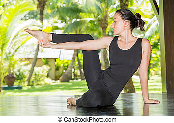 Young woman is practicing yoga and pilates on nature....