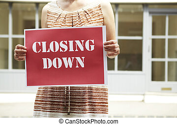 Woman Standing Outside Empty Shop Holding Closing Down Sign