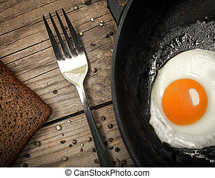 Fried egg on a cast iron pan - Closeup of fried egg on a...