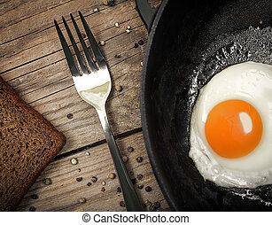 Fried egg on a cast iron pan - Closeup of fried egg on a...