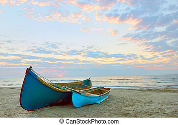 two Fishing boats and sunrise on Black Sea beach