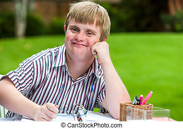 Boy with down syndrome at desk holding glasses. - Close up...