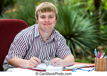 Boy with down syndrome at desk outdoors. - Close up portrait...