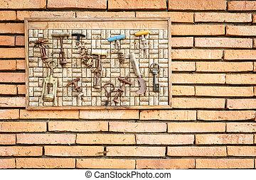 A collection of dozen vintage corkscrews hang on the brick...