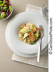 Risotto with vegetable and chicken on white plate