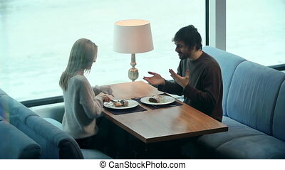 Enjoy Your Meal - Side view of young couple eating and...