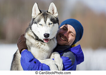 Happy man with a husky at winter time