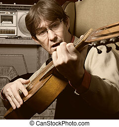 Bard man in glasses playing guitar. Guitarist sings a song about