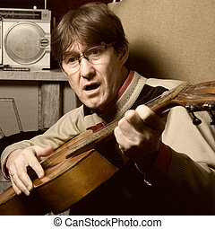Bard man in glasses playing guitar. Guitarist sings a song...