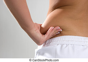 Saddlebag Flab - Young woman pinches the fat on the side of...