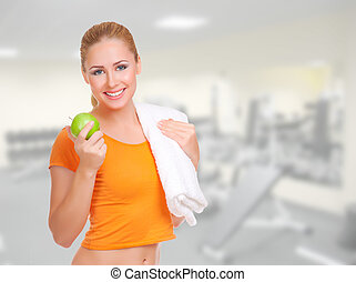 Young woman with green apple and towel