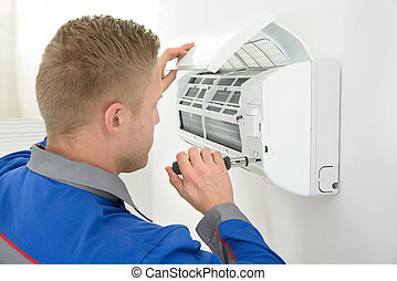Technician Repairing Air Conditioner - Portrait Of Young...