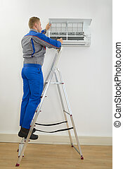 Male Technician Repairing Air Conditioner Standing On...