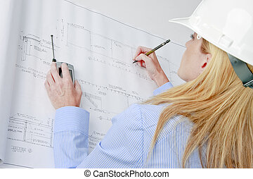 Female architect working on blue prints - A mature female...