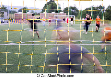 Playing soccer - Soccer players and net in the foreground