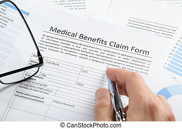 Hand With Pen Over Medical Claim Application - Close-up Of...