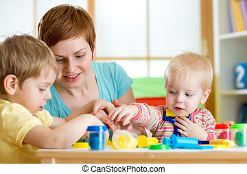 kids and mother playing colorful clay toy - kids and woman...