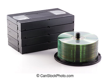 Dvd versus video. - Videotapes and a pile of DVDs on a white...