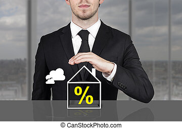 businessman holding protective hand above building...