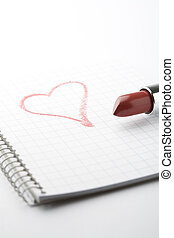Lipstick and heart on notepad. - A close-up of a tube of red...