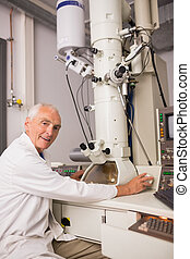 Biochemist using large microscope and computer at the...