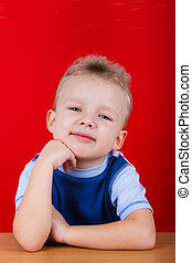 Small boy in blue T-shirt, sitting at the table On a red...
