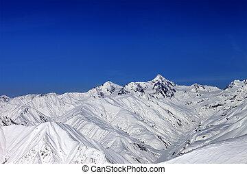 Snowy mountain peaks in sun day