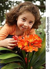 Little girl in a garden of clivia miniata