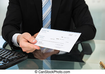 Midsection Of Businessman Showing Cheque - Midsection of...