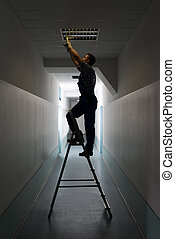 Electrician On Stepladder Installs Lighting To The Ceiling -...