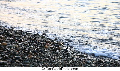 Small sea waves run on the stony seashore