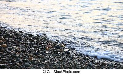 Small sea waves run on the stony seashore