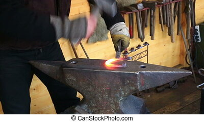 smith forges a horseshoe on an anvil in a smithy