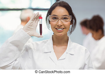 Pretty science student smiling and showing vial at the...