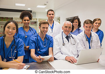 Medical students and professor smiling at camera at the...